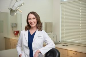 A smiling female dermatologist standing next to a chair where she treats her patients.