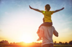 A parent with their child on their shoulders looking out into an open field during the sunset.