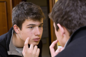 teenage boy looking at the mirror as he's picking at his face