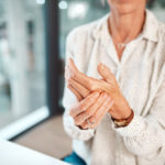 Older woman sitting at her desk holding her hand in pain from carpal tunnel syndrome.