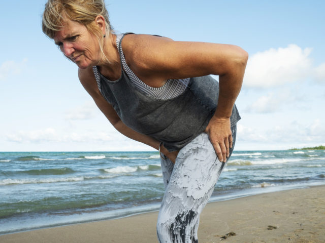 A mature woman in her fifties experience hip pain during a morning run