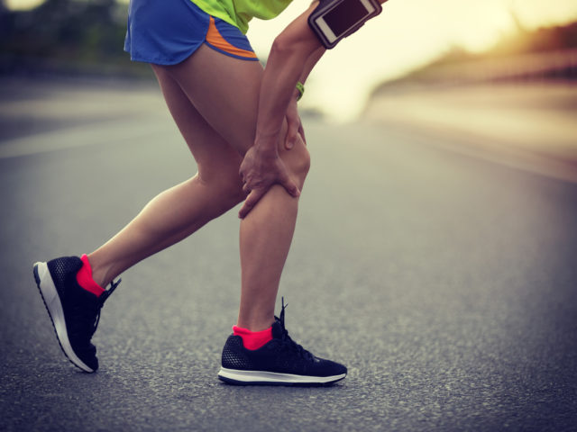 Sportswoman suffering from knee pain while running on city road