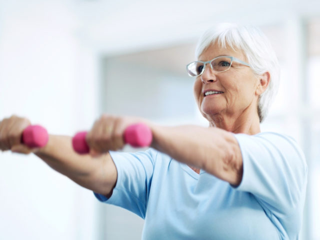 senior woman working out using dumbbells at home