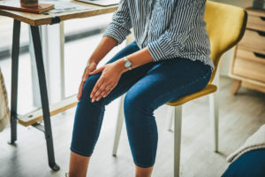 Woman in blue jeans sitting in a chair and holding her knee demonstrating pain coming from the area.