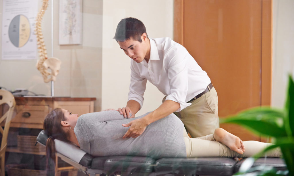 chiropractor adjusting a young woman's spine
