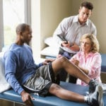 Physical therapists examining patient