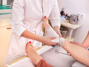orthopedic doctor taking care of patient suffering from foot pain