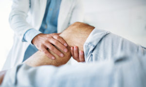 A man getting his knee pain checked out by an orthopaedist.