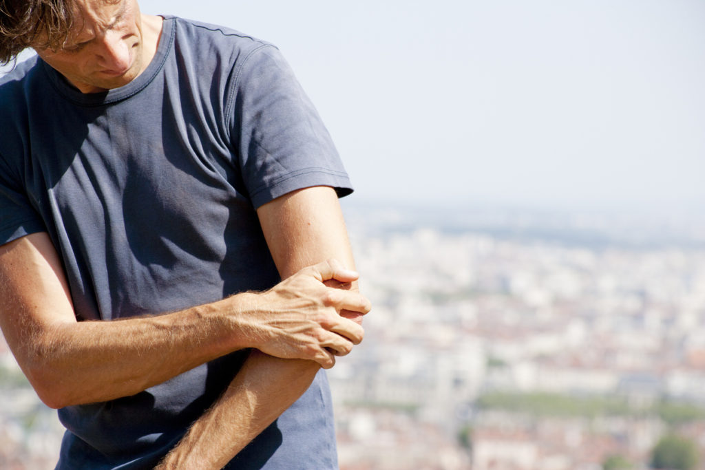 A man holding his arm in pain from tennis elbow. He's standing in front of a view of the city.