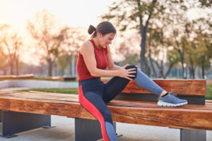 Young sportswoman having pain / injury during exercise and jogging in the park
