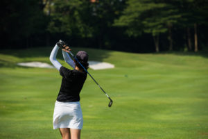 A female golfer swinging at the ball.