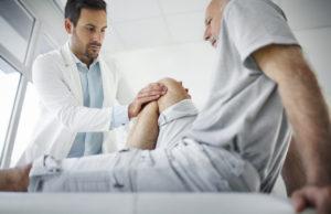 Orthopedic doctor diagnosing knee condition