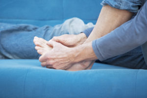 Woman sitting down on the couch holding her foot in pain.