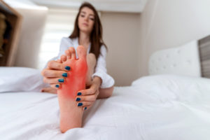 Woman is holding the sole of her aching foot