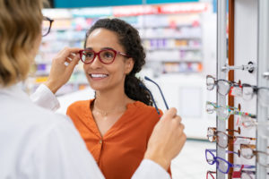 A woman getting fitted for eye glasses with an eye doctor.