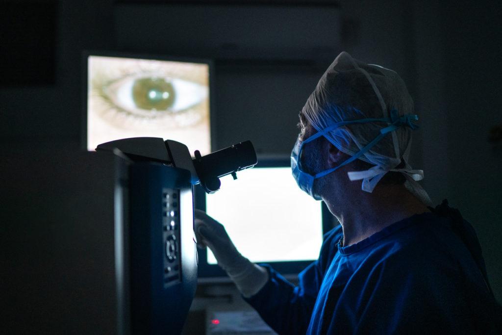Doctor examining eye in the dark