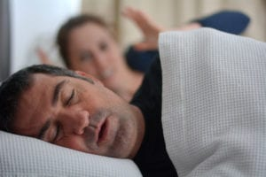 Woman suffers from her male partner snoring in bed
