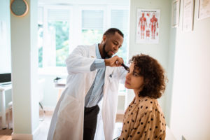 Woman getting her ear checked by doctor