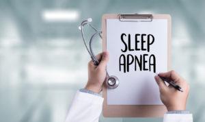 A doctor holding a clipboard that says sleep apnea on it.