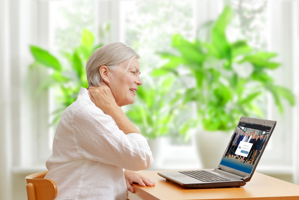 woman with neck pain logging in to a telemedicine meeting