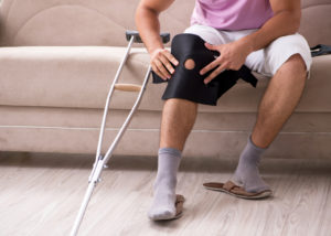 Man with knee brace going through post-op recovery at home