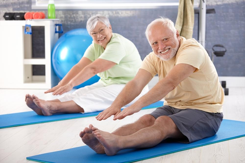 Elderly couple stretching on yoga mats
