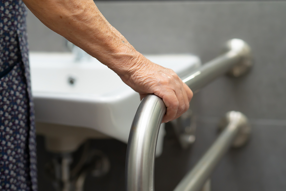 Elderly woman holding onto grab bar in bathroom for fall prevention