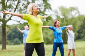 Older adults stretching the shoulders and back