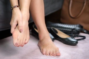 Beautiful working woman's hand massaging her bunion toes in bare feet to relieve pain.