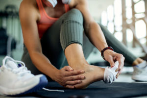 Close-up of athletic woman injured her foot during workout at the gym