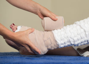 putting bandages on a injured ankle