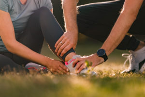 man assisting his wife with ankle pain during sports training in nature