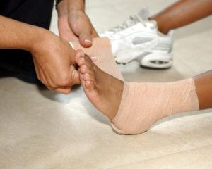 mother bandaging child's ankle sprain