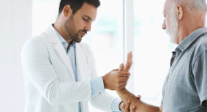 An elderly man getting his hand looked at by a doctor because he is having wrist pain.