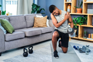 A man lifting weights in his living room while he is holding his injured shoulder due to pain.