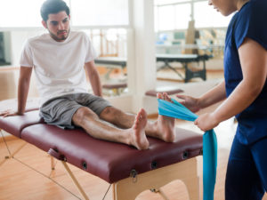 sports medicine physician treating young man's foot with elastic band