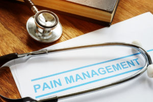 Pain management documents and stethoscope with book.