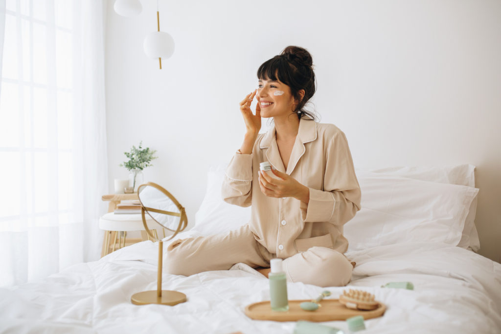 Smiling woman applying face cream sitting on bed
