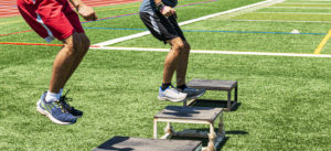 athletes jumping on to plyo boxes