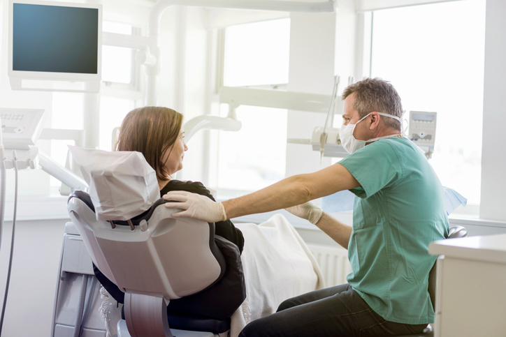 Dentist talking to female patient in clinic