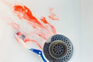 Blood on toothbrush on background of sink.