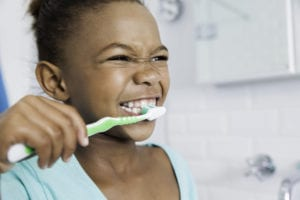 Beautiful young girl brushing her teeth.