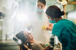 Young happy woman talking to a dentist before dental procedure.