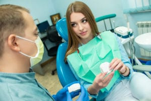 A girl is sitting in the dental chair and looking at a man doctor who is talking to her. dental clinic