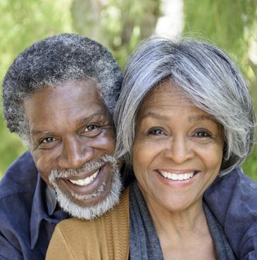 older couple smiling after getting their affordable dentures