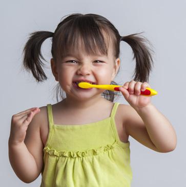 small girl brushing her teeth