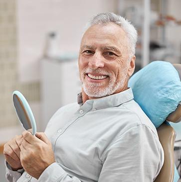 man smiling after getting dental crowns