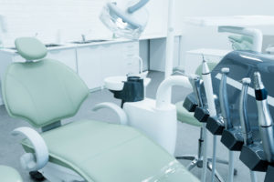 An empty dental office with a green chair and equipment.