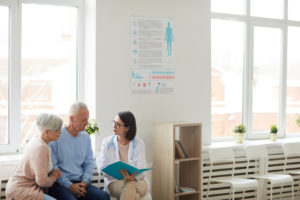Female physician speaking with an elderly couple on a bench inside of a hospital.