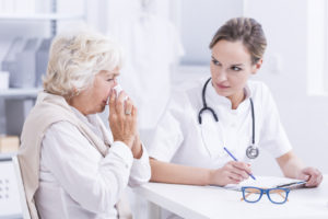 Elderly woman blowing her nose as she talks to a female allergist who is writing down her symptoms.